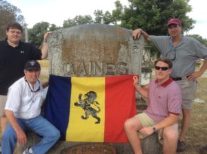 "From left, Brothers Rony (""Dancing Bro"") Young '16, John McNeil '79, Jeffrey Kintz '16, and Semmes Favrot '82 with the DKE flag at the grave of Psi Brother Rueben Reid Gaines 1855, in Austin, Texas, August 7, 2015."